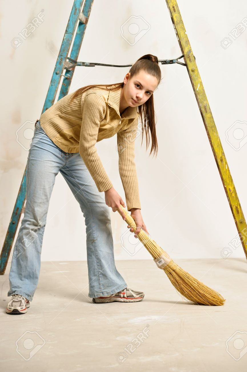 teen girl with a broom sweeping the floor Stock Photo - 17480848