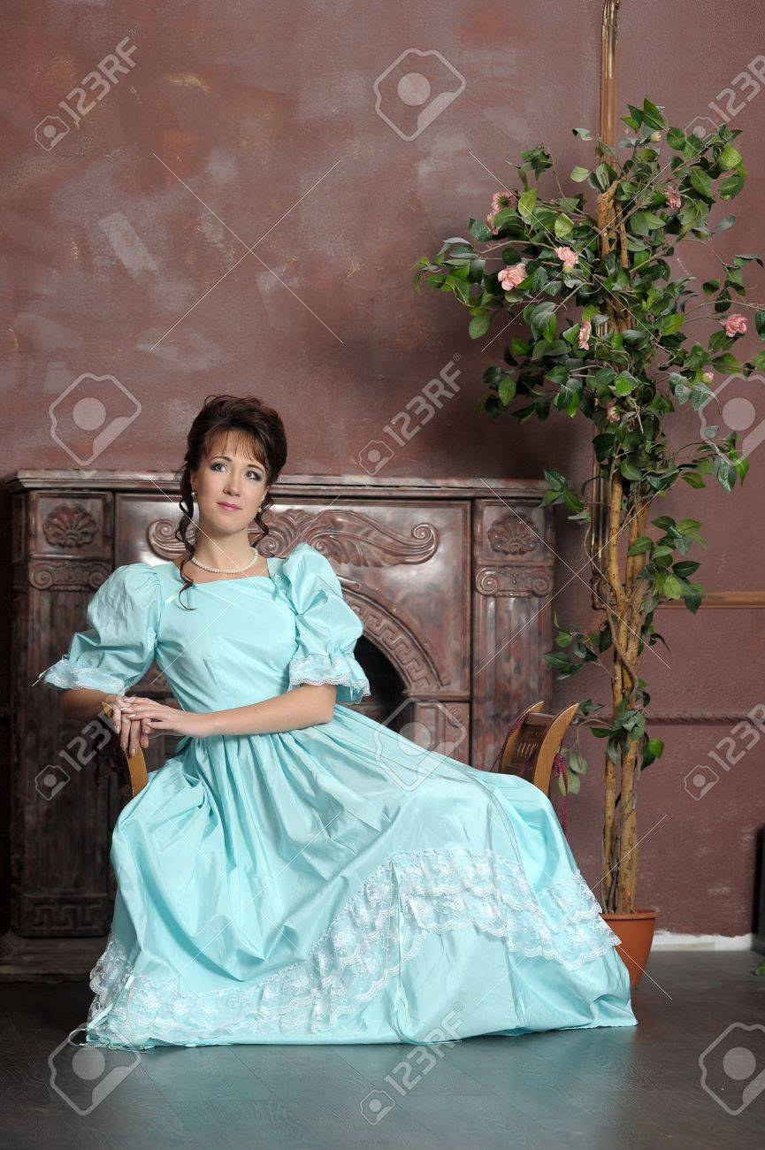 The young woman in an ancient blue dress with a fan in hands Stock Photo - 12676119