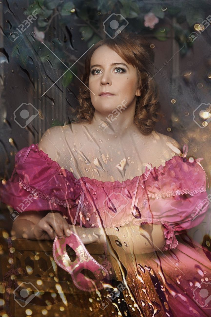 portrait of the woman in a medieval dress behind glass with rain drops Stock Photo - 13153653
