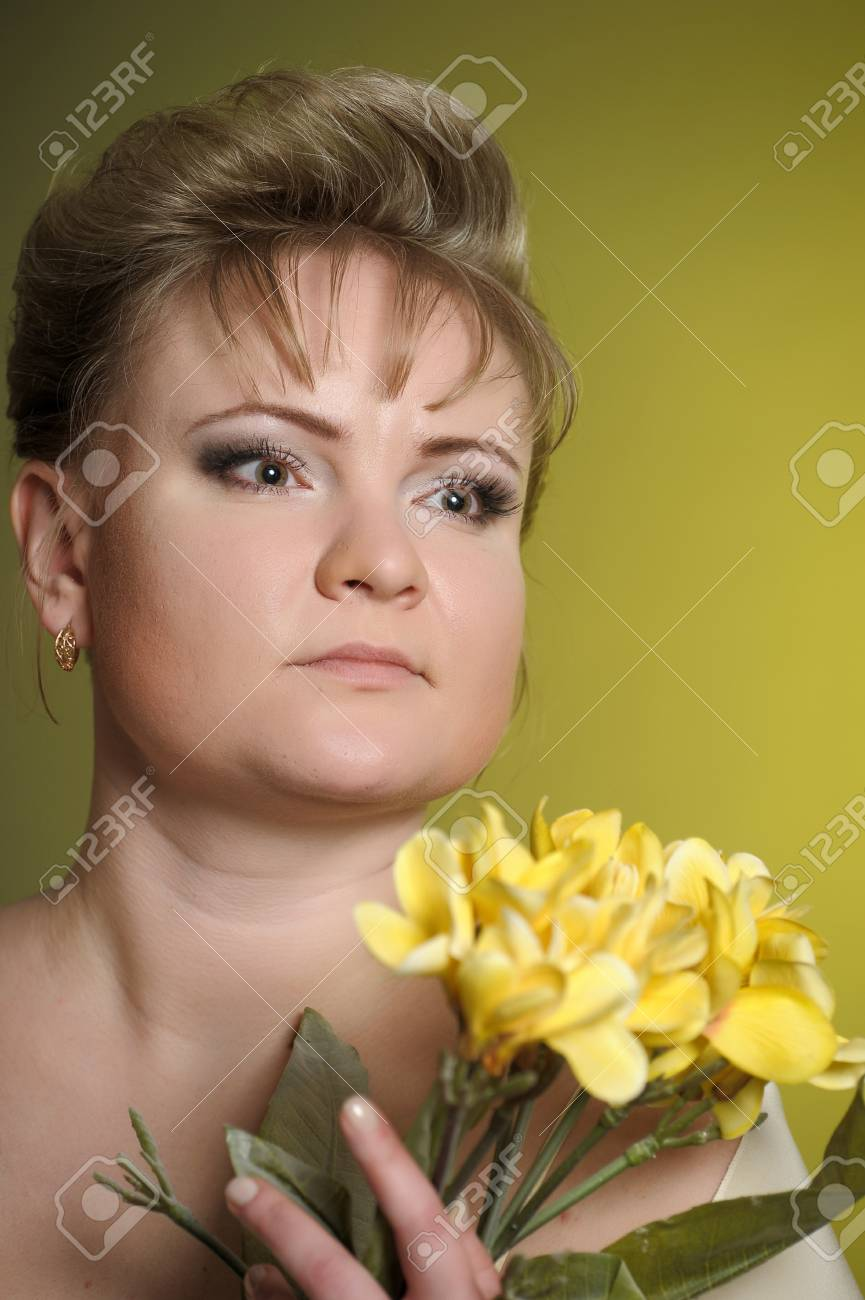 the woman in a yellow dress with flowers in hands Stock Photo - 13218895