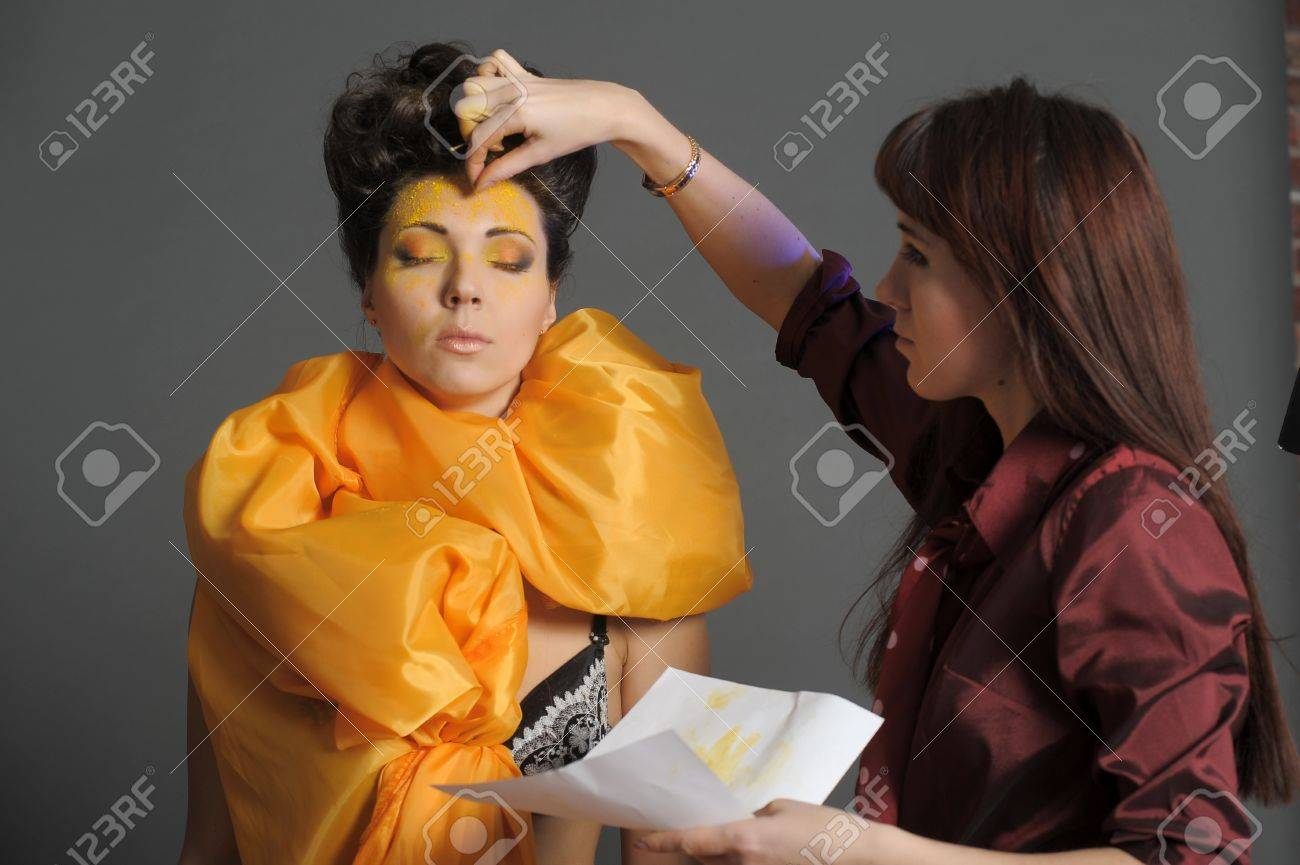 Model getting some vivid make-up applied before a fashion photoshoot Stock Photo - 13147085