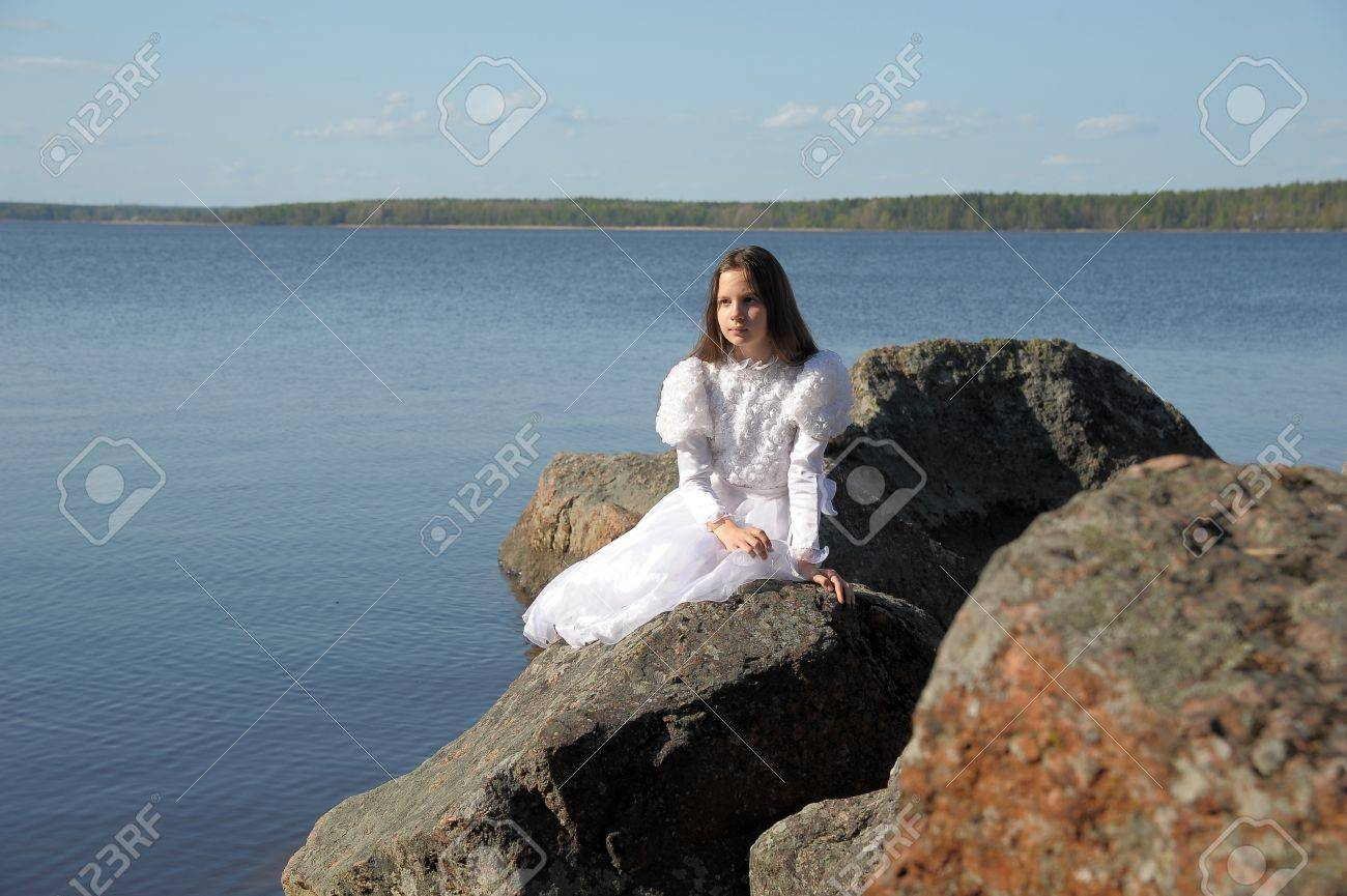 Beautiful girl sits on a cliff at sunset watching the sea Stock Photo - 13553827