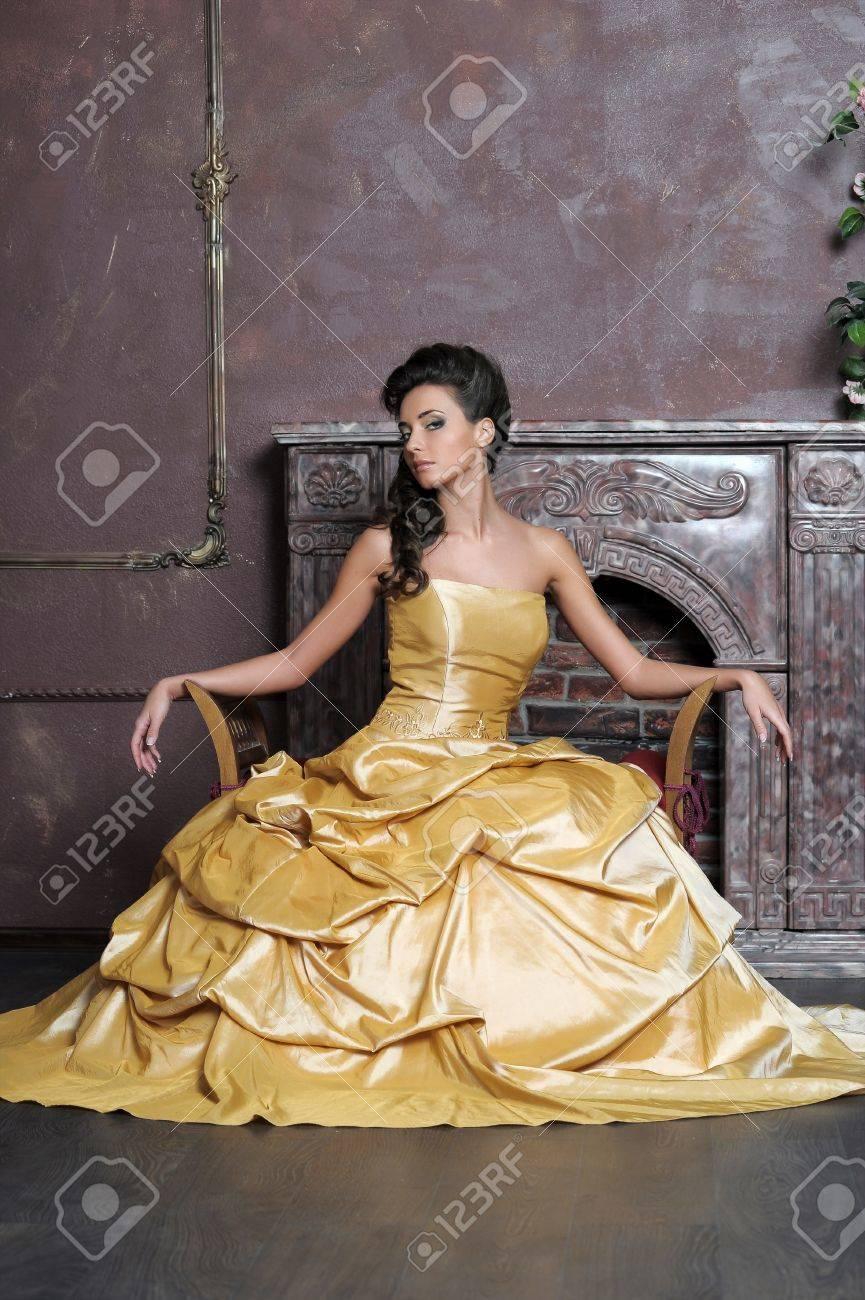 Elegant  beauty posing in a golden dress Stock Photo - 13837725