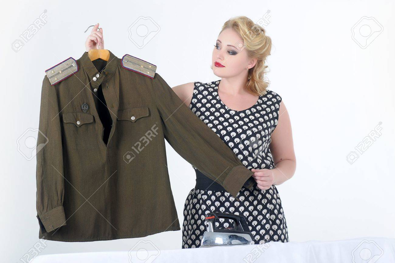the young girl irons a soldier s blouse Stock Photo - 14167663