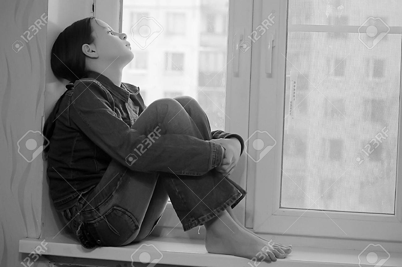 The sad girl the teenager at home on a window sill Stock Photo - 14190823
