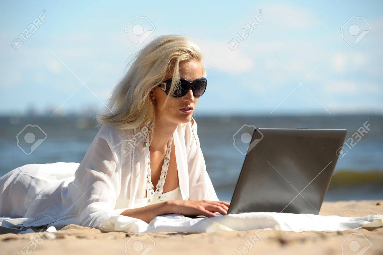 Happy blonde woman at a beach with a laptop Stock Photo - 14577549