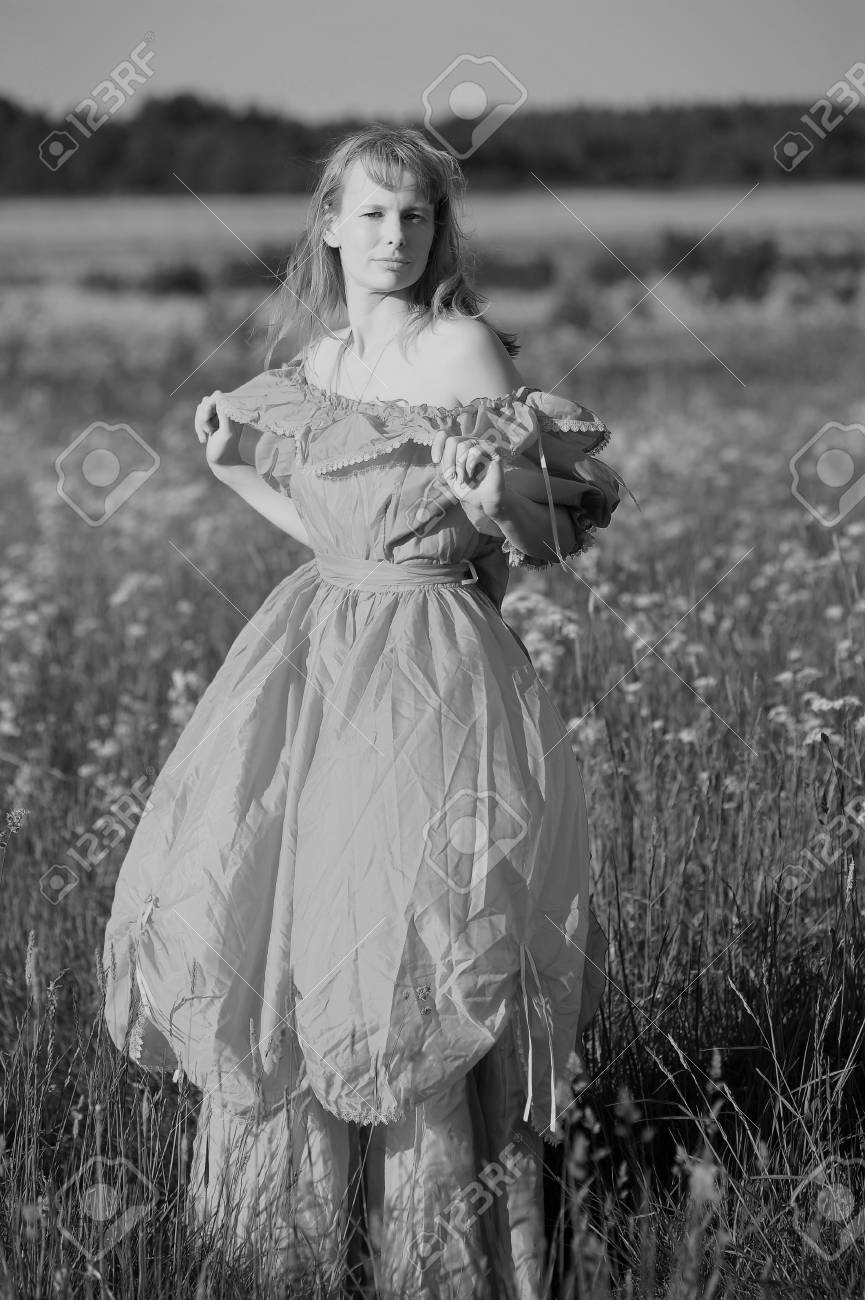 young woman in an old dress in the middle of the field Stock Photo - 14577821
