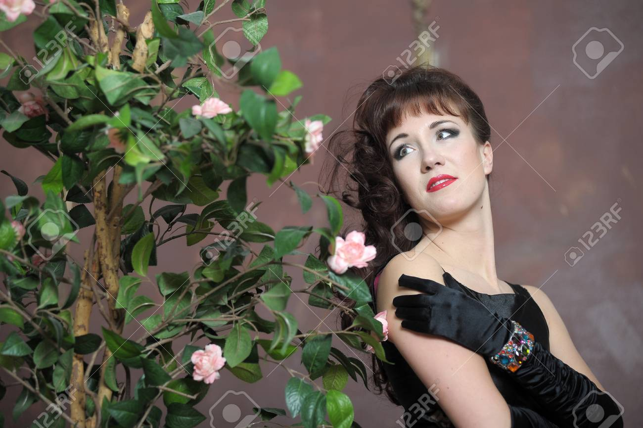 young woman in elegant dress next to a bush of roses Stock Photo - 14996332