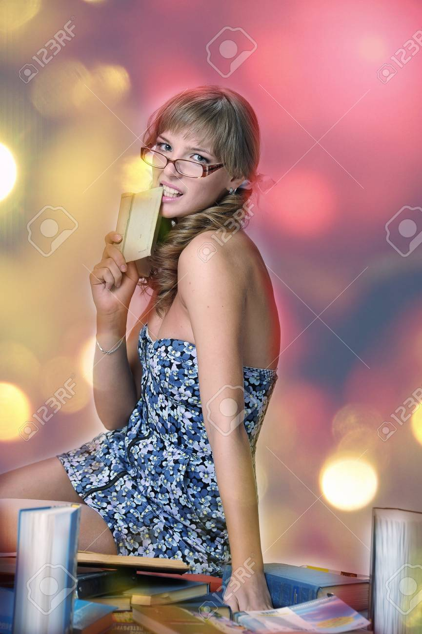 Young student with glasses and a pile of books Stock Photo - 14902575