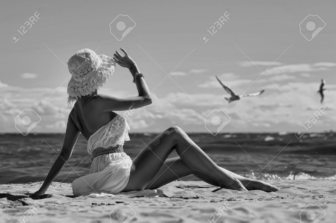 the girl in a dress and hat on the beach Stock Photo - 15014575