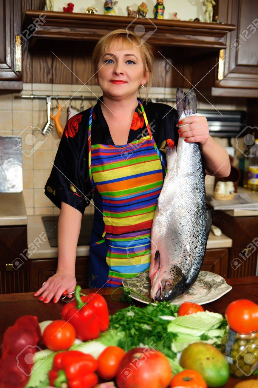 The woman fish at itself on kitchen Stock Photo - 15148541