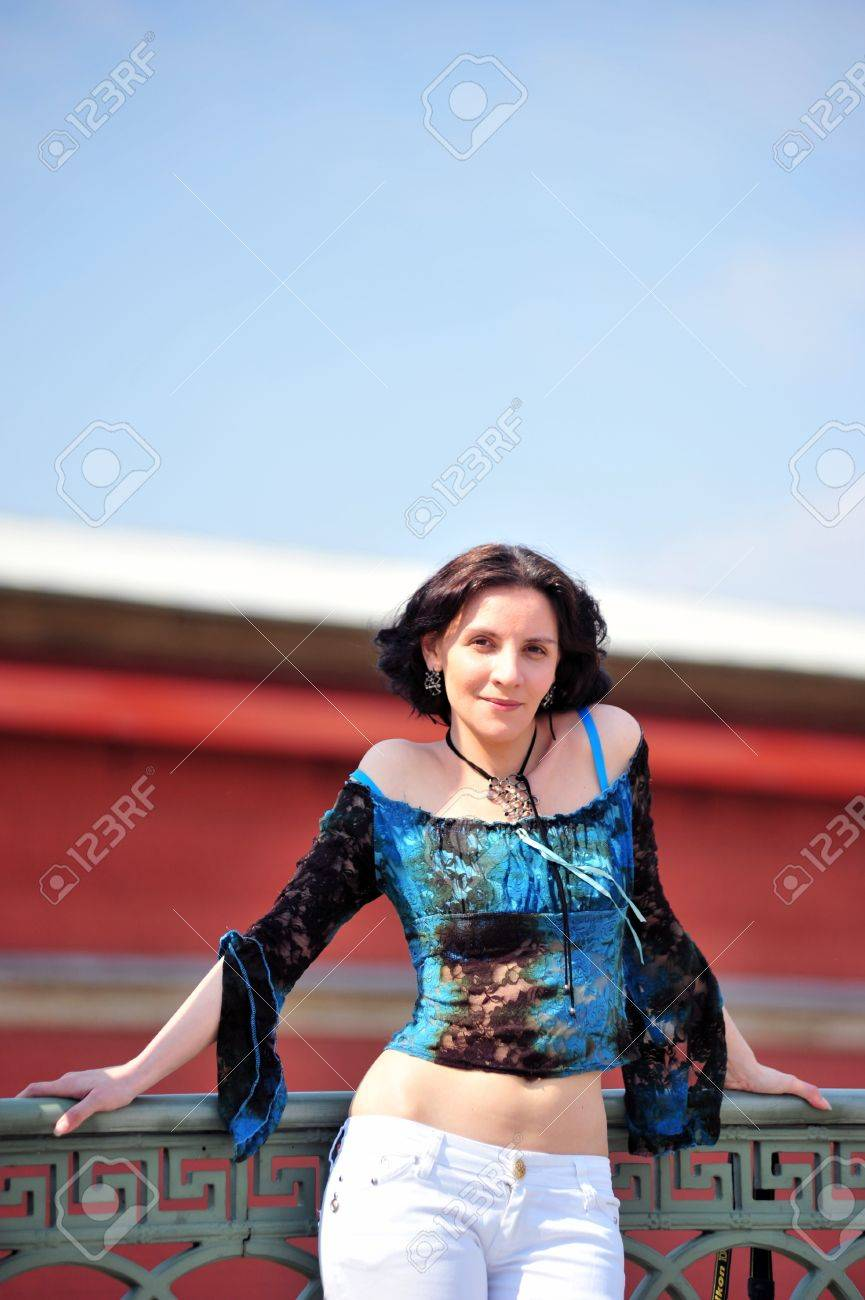 glamorous young woman in blue blouse leans on the railing Stock Photo - 19029946