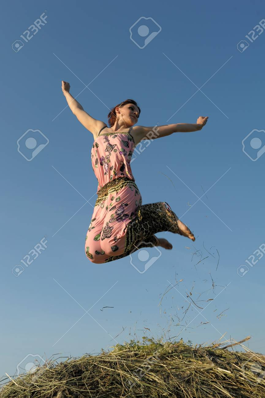 Girl jumping up on straw roll Stock Photo - 15483673
