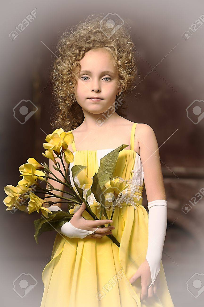 Girl in a yellow dress with a flower in hand Stock Photo - 17935315