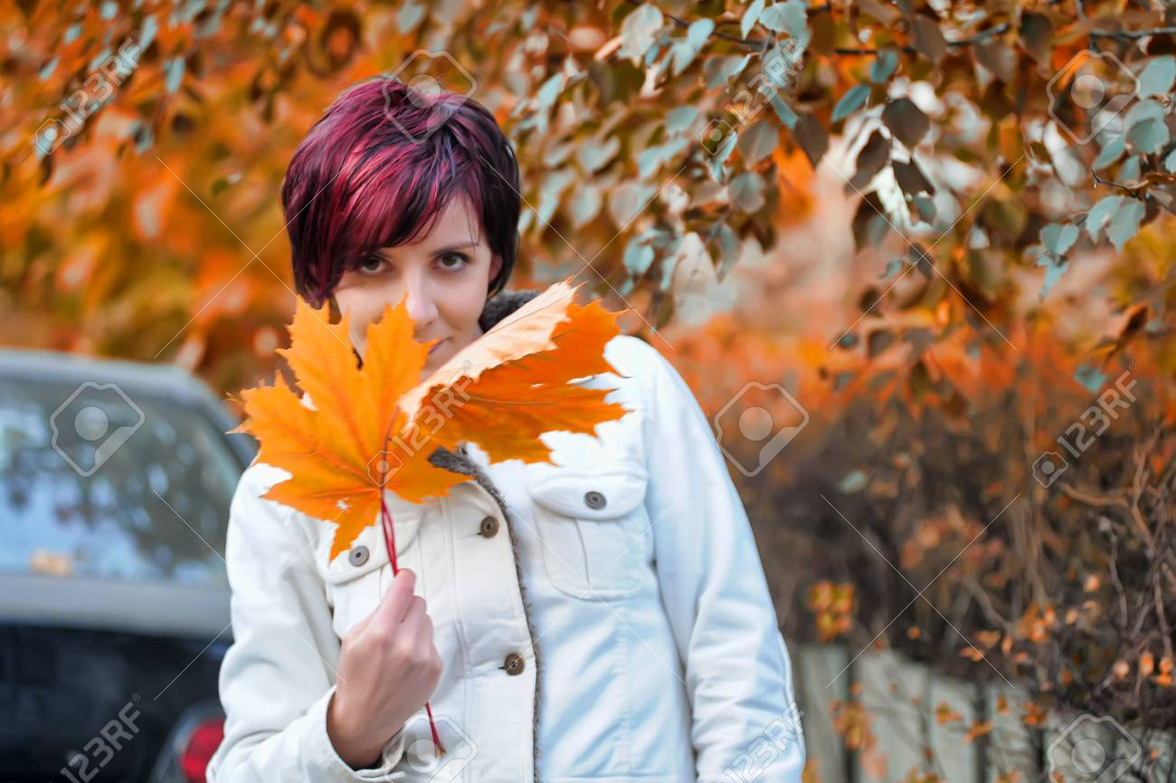 Young woman with autumn leaves in hand Stock Photo - 15479378