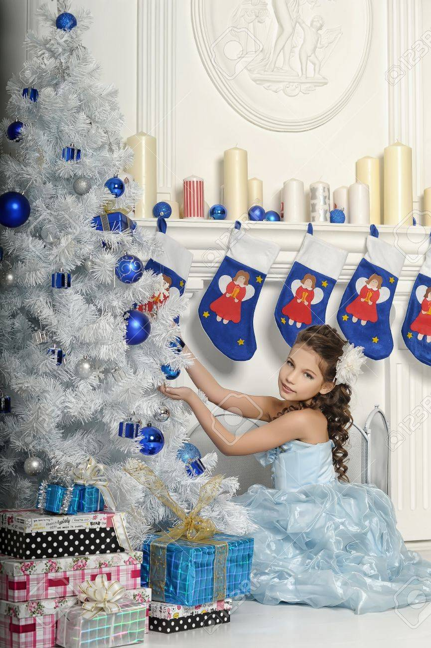 girl with gifts near a Christmas tree Stock Photo - 19026563