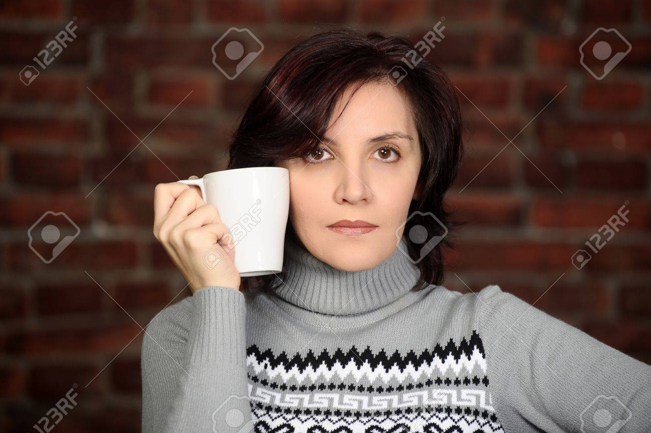 young woman in a gray sweater with a cup in hands Stock Photo - 17962687