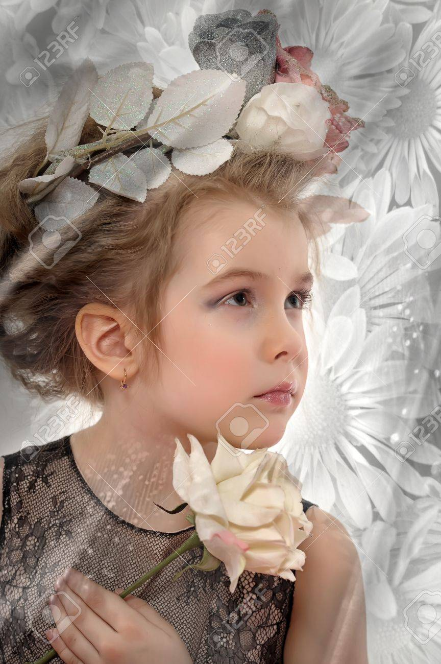 little girl with flowers on her head and a white rose in her hand Stock Photo - 19283224