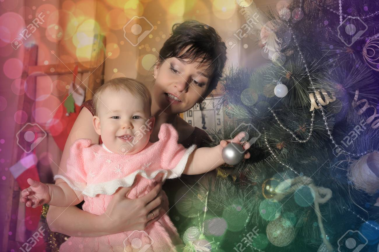 mom with a little girl in the arms of a Christmas tree Stock Photo - 18229478