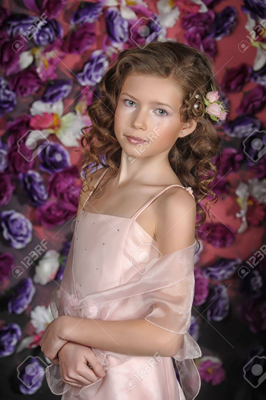 girl in a pink dress on a background of an arch of flowers Stock Photo - 19000544
