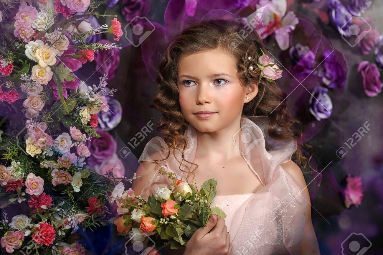 girl in a pink dress on a background of an arch of flowers Stock Photo - 19000550