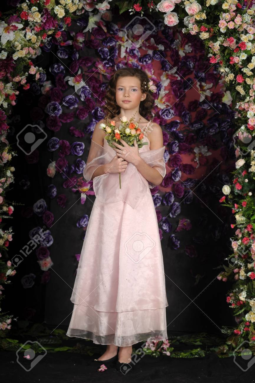 girl in a pink dress on a background of an arch of flowers Stock Photo - 19121431