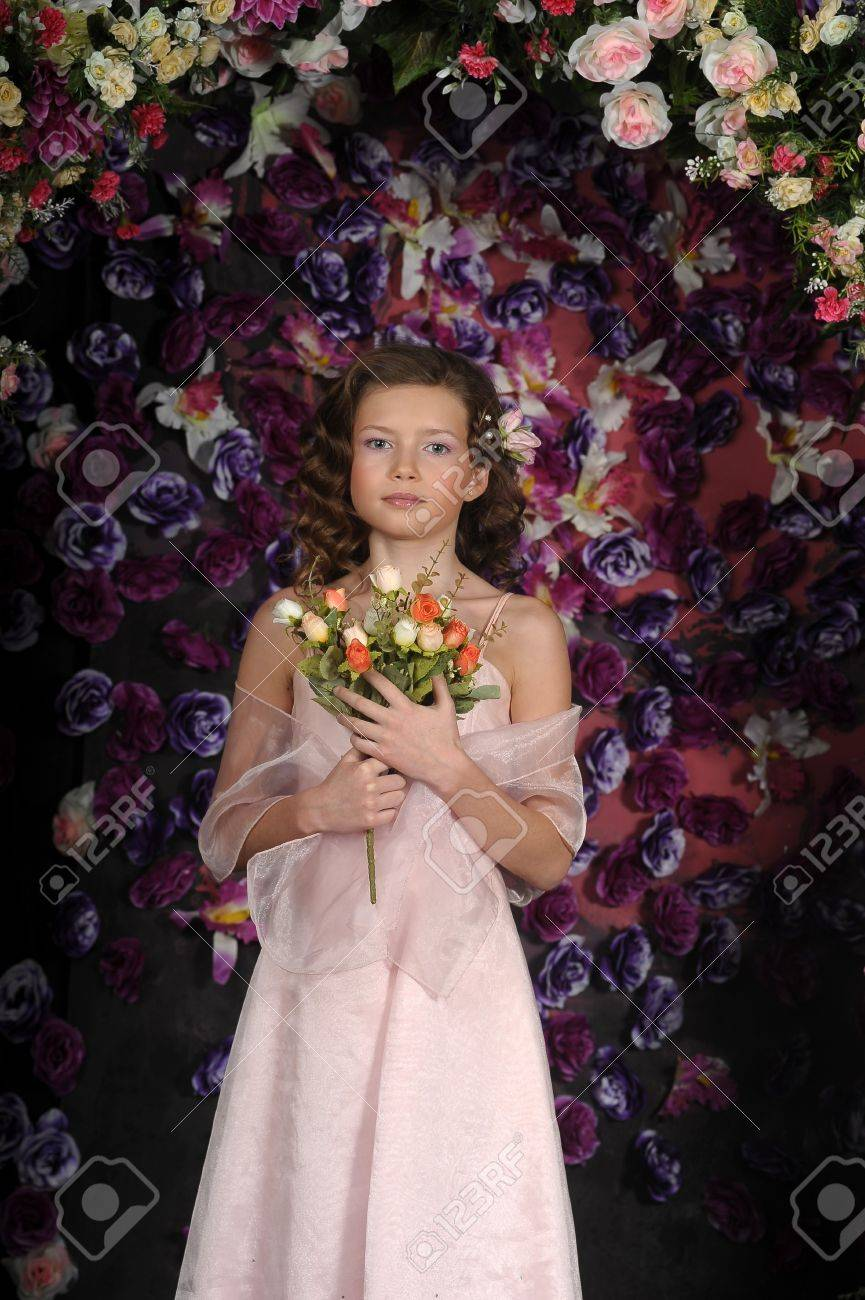 girl in a pink dress on a background of an arch of flowers Stock Photo - 19121520