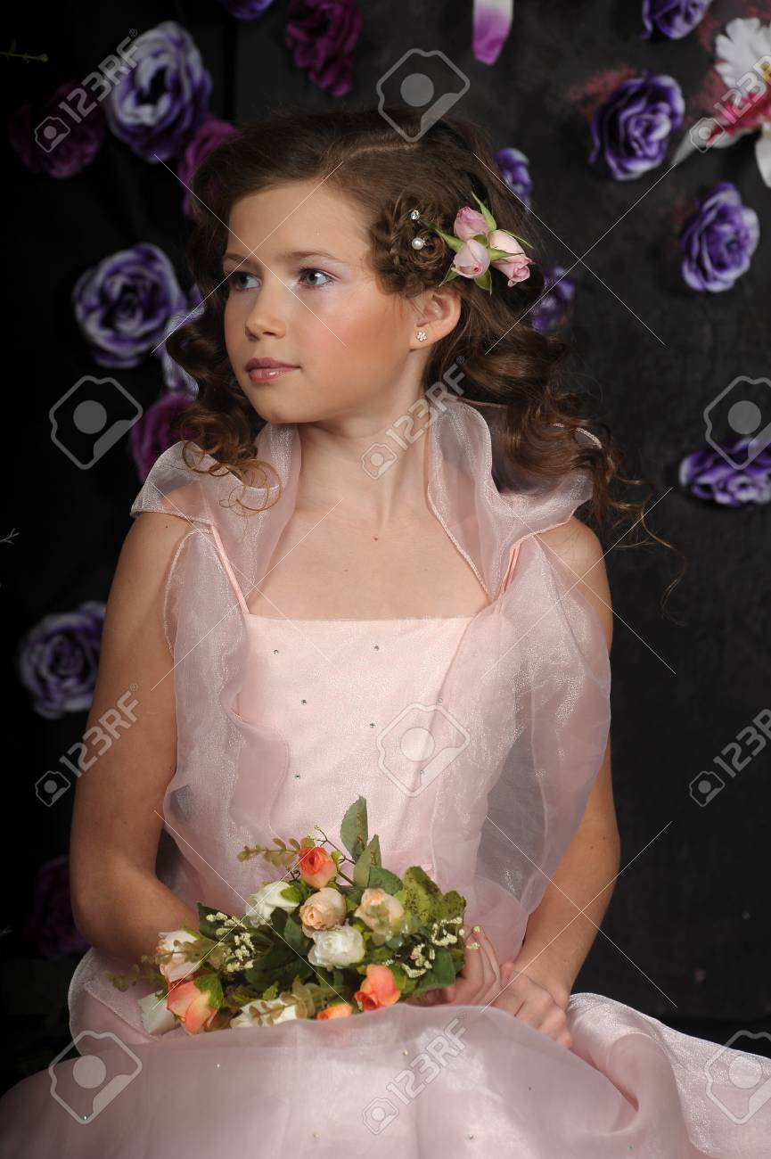 girl in a pink dress on a background of an arch of flowers Stock Photo - 19121505
