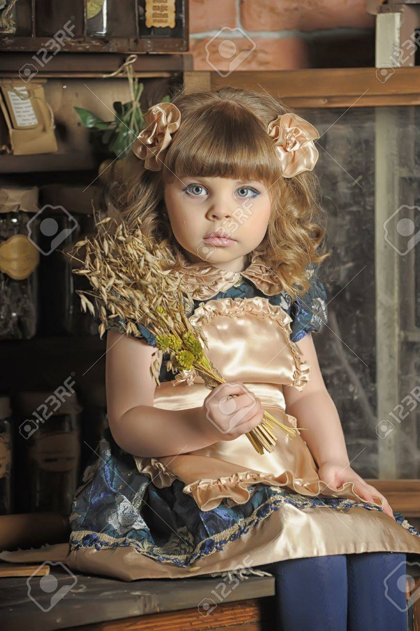 a little girl dressed in retro style on the old kitchen Stock Photo - 19204200