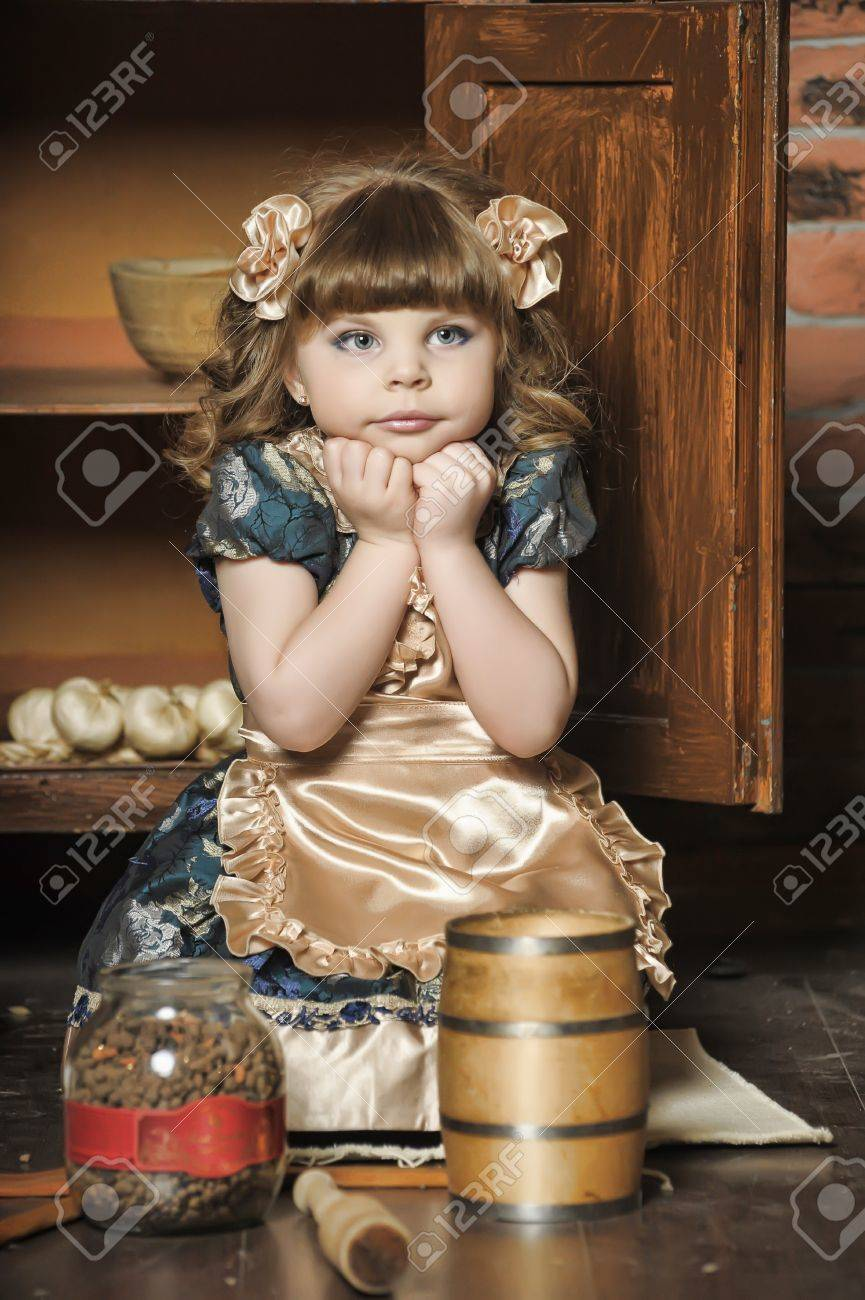a little girl dressed in retro style on the old kitchen Stock Photo - 19204195