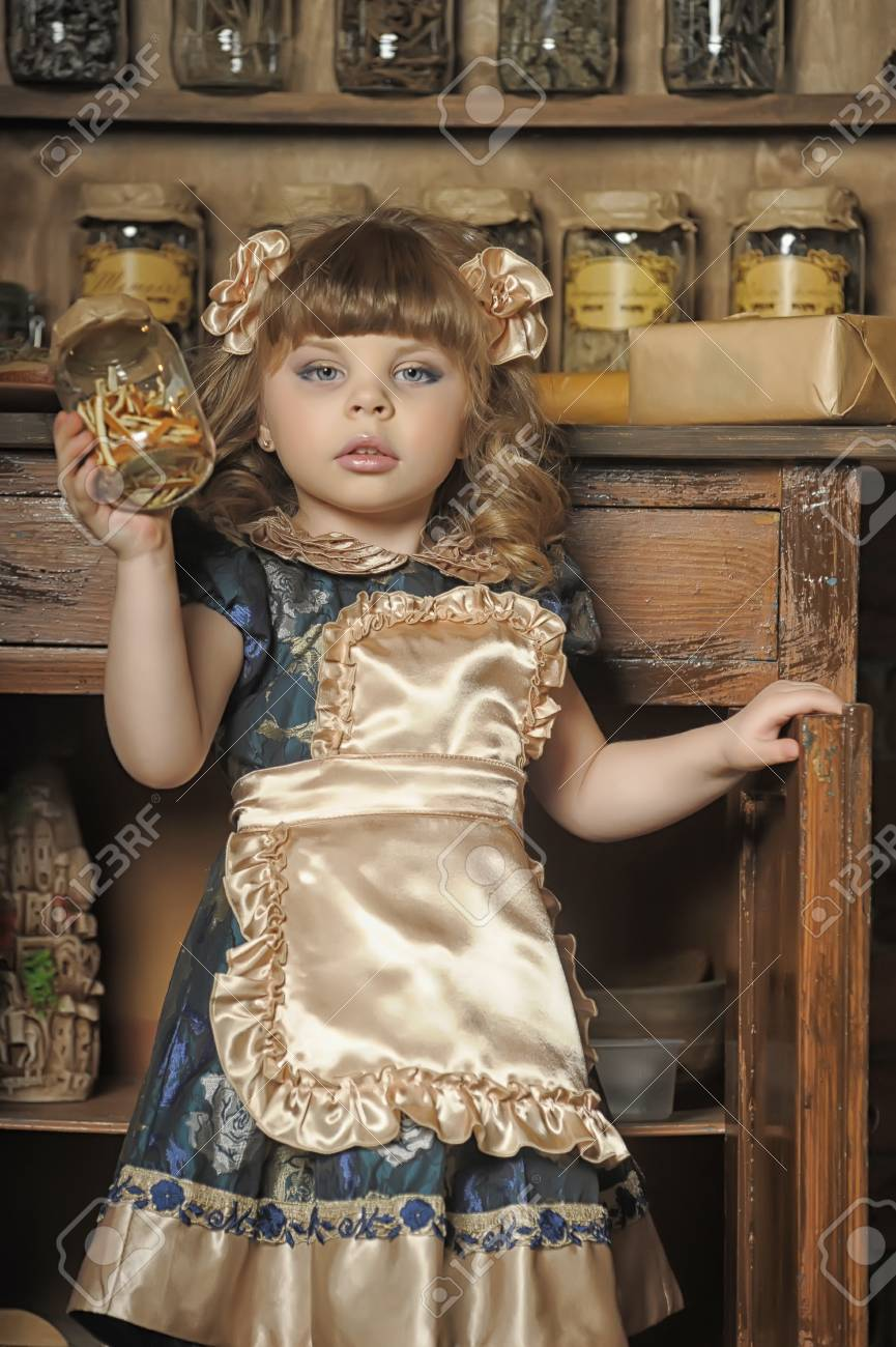 a little girl dressed in retro style on the old kitchen Stock Photo - 19204203