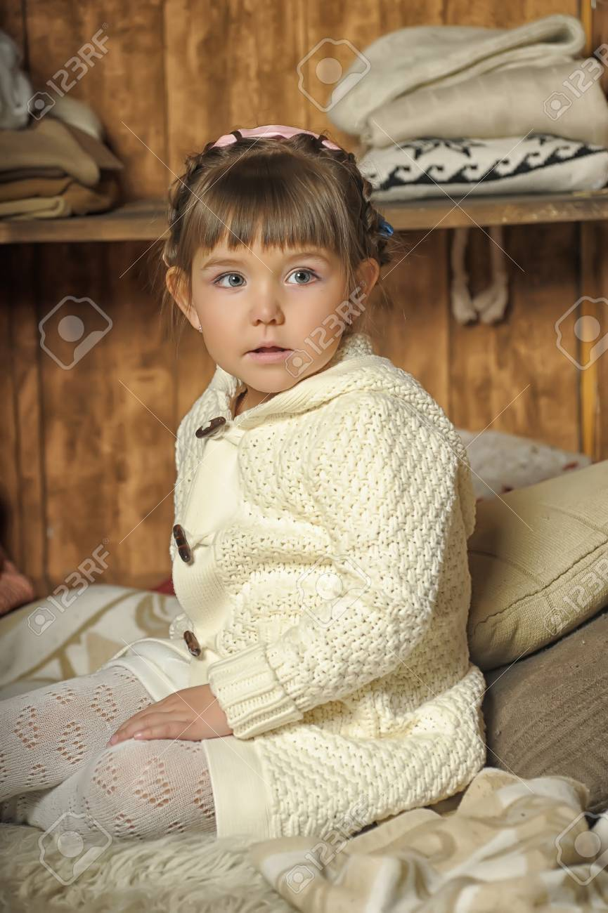 the little girl next to the wardrobe with warm clothes Stock Photo - 19338770