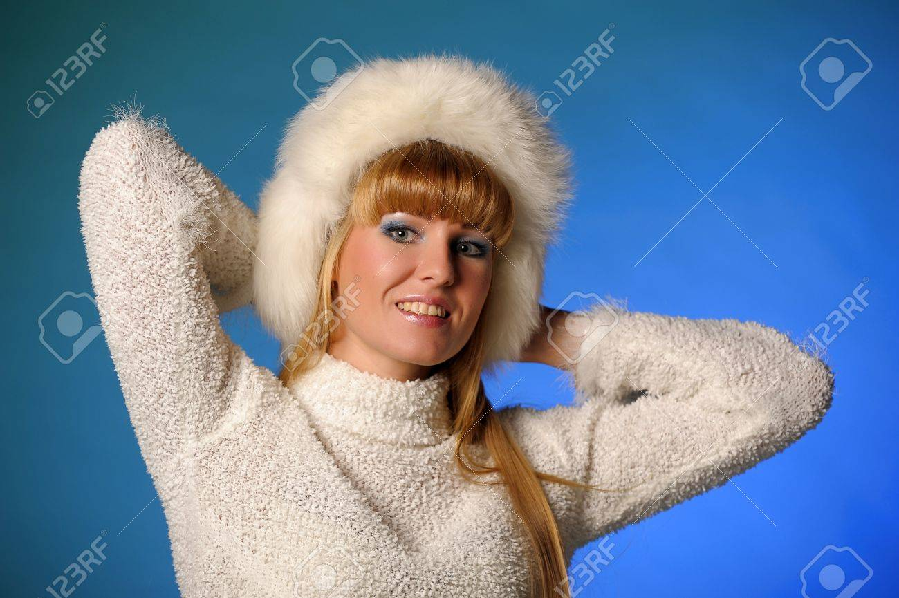 beautiful blond woman in a fur cap on a blue background Stock Photo - 21805252