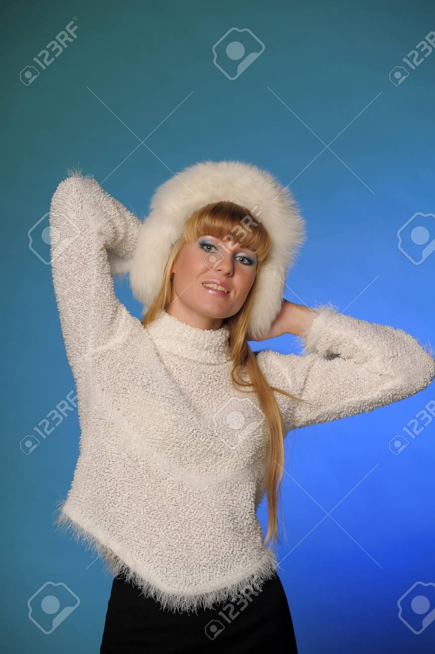 beautiful blond woman in a fur cap on a blue background Stock Photo - 21805254