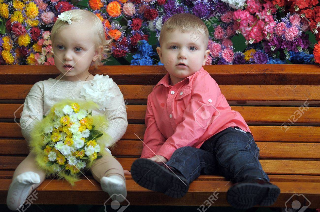 Children on a bench with flowers in the background Stock Photo - 21741981