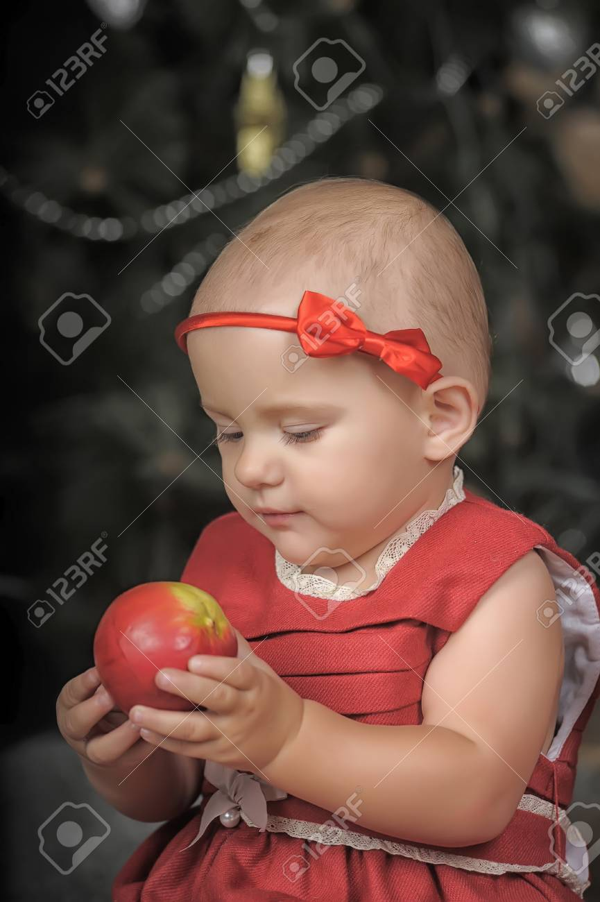 9fe7d7a1bf7 Girl in red dress with an apple in her hand. Stock Photo - 33554206