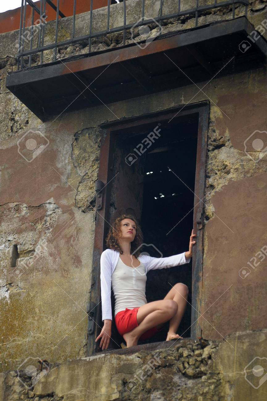 young woman in the window of a ruined house Stock Photo - 25817103