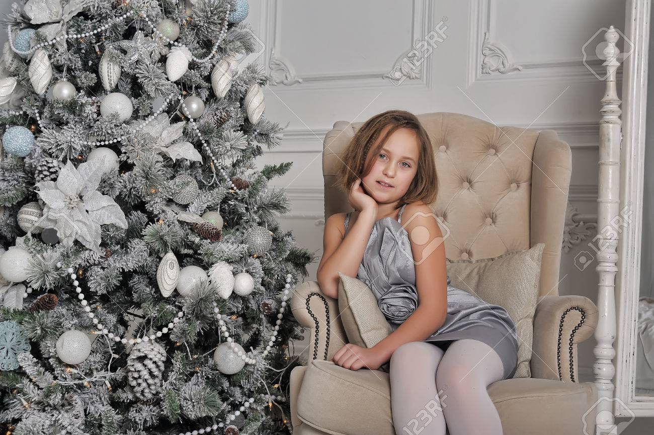 Grey Christmas Tree Girl In A Pale Grey Dress Sitting In A Chair At The Christmas