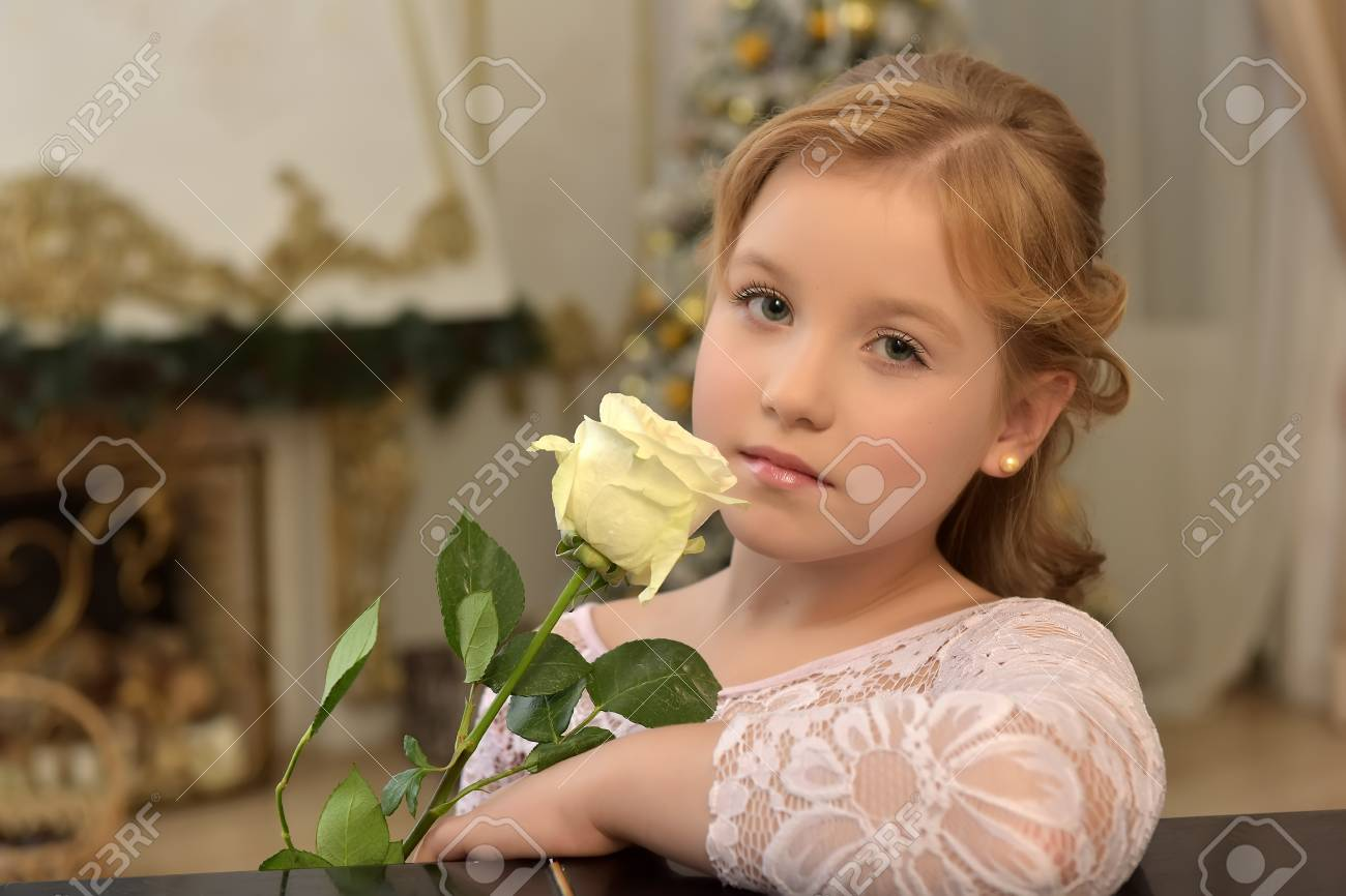 portrait of a teen blonde with a white rose in a lace blouse - 115269130
