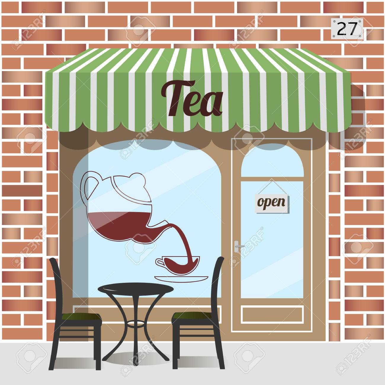 Tea shop building. Facade of brick. Tea sign sticker on window. Table and chairs at the fore. - 57259595