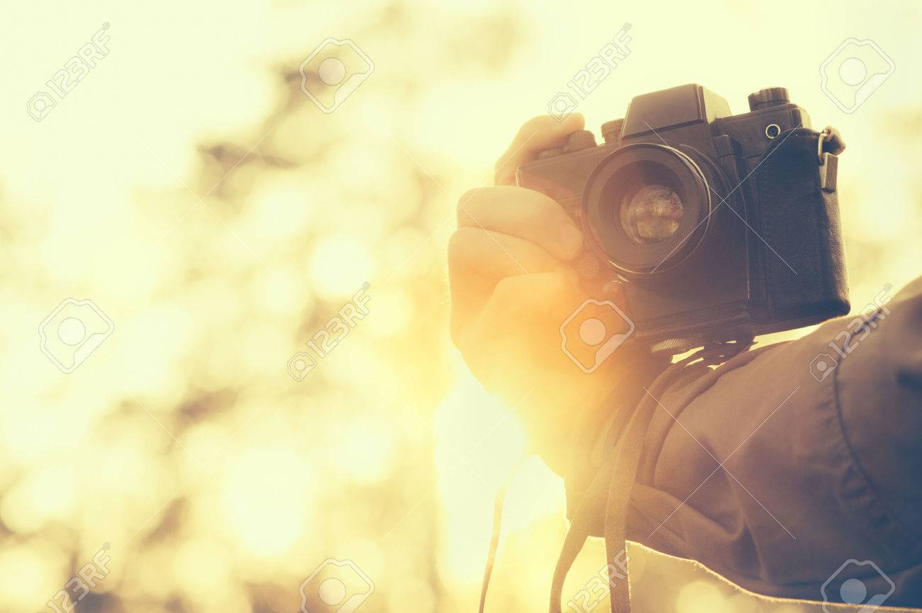 Man hand holding retro photo camera outdoor hipster Lifestyle with sunset lights on background film colors Stock Photo - 55631094