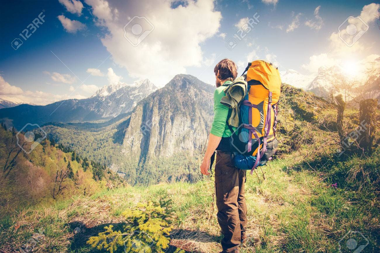 Young Man Traveler with backpack relaxing outdoor with rocky mountains on background Summer vacations and Lifestyle hiking concept - 55632286