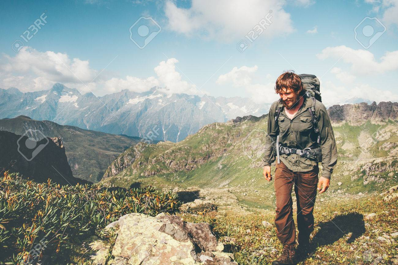 0c5b00e1f9f6 Stock Photo - Traveler Man hiking with backpack Travel Lifestyle concept  adventure summer vacations outdoor mountains range landscape on background