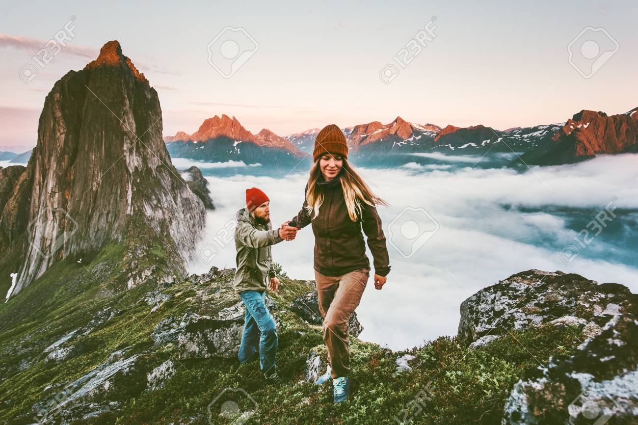 Happy Couple holding hands traveling together hiking in Norway healthy lifestyle concept active vacations outdoor Segla mountain sunset landscape - 107653928