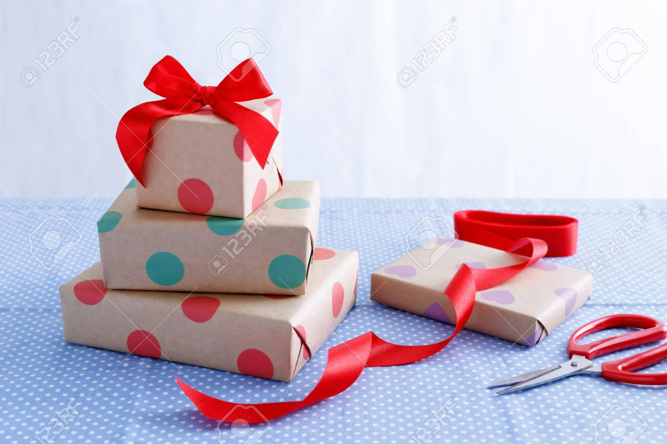 Presents For Birthday With Wrapped Boxes And Red Ribbon On Table