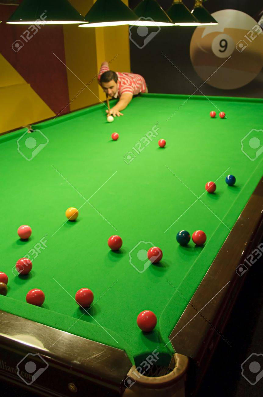 Young man playing snooker in a pub (balls scattered on the table) (view from a pocket) Stock Photo - 6281525