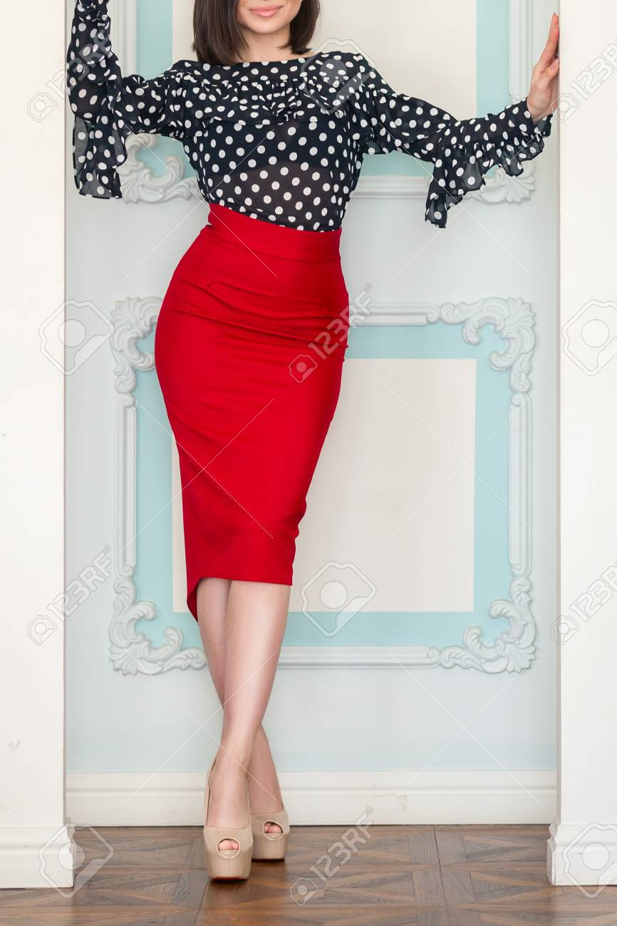 35b1fa2d40 Stock Photo - Young beautiful slender girl in red skirt and black and white  blouse with high heels posing in studio