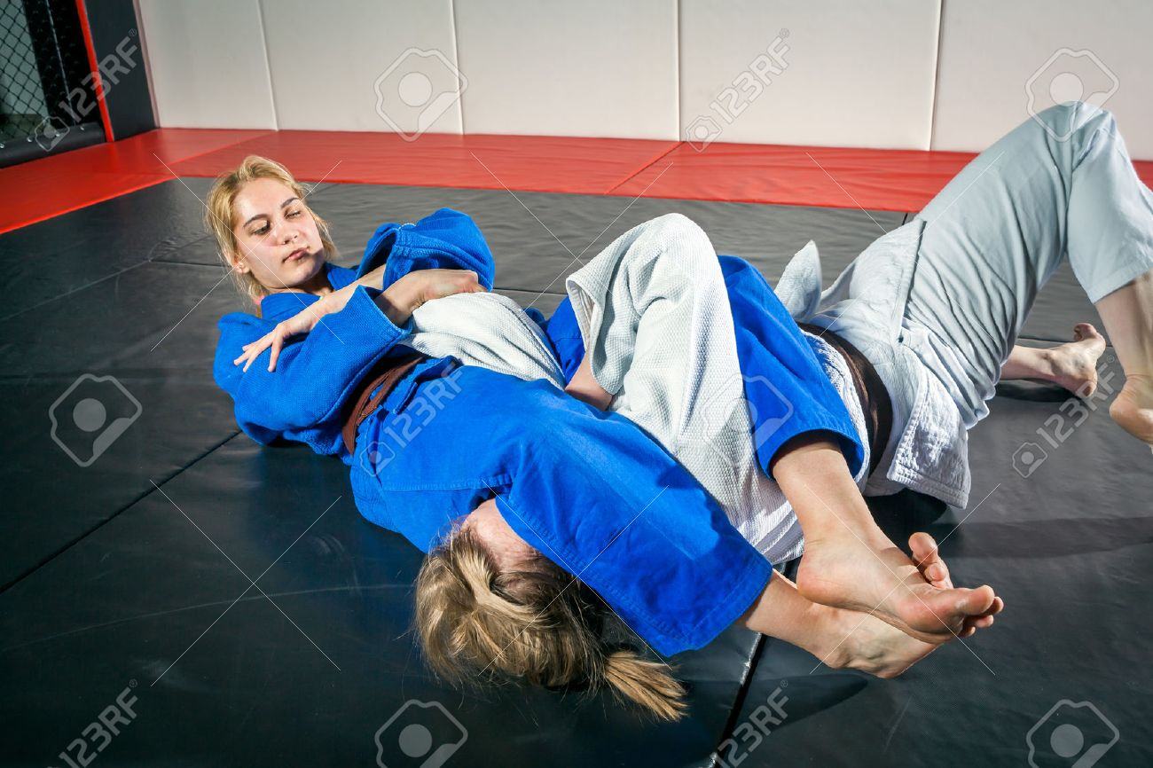 Two women are fighting on tatami. Judo, Jiu Jitsu. Stock Photo - 80944974