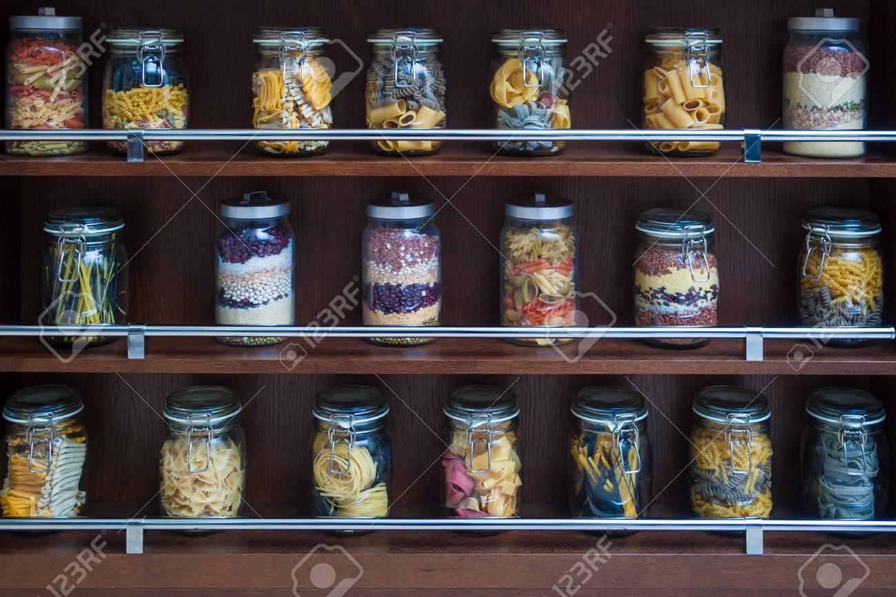 Sur les étagères en bois se trouvent des bocaux en verre contenant divers  types de pâtes, spaghettis, haricots et céréales de couleurs variées pour  le