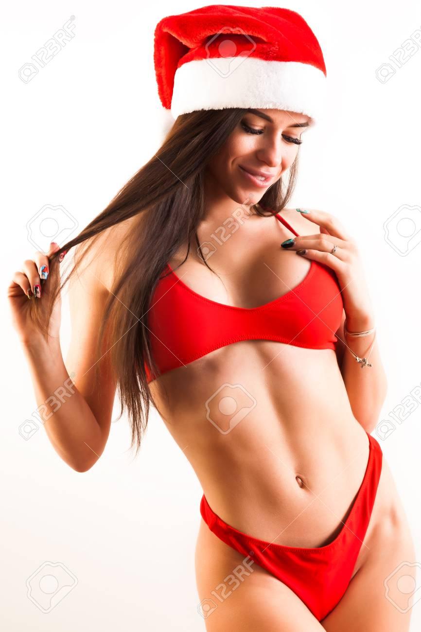 63c52ce67 Modèle de fitness jeune femme brune en maillot de bain rouge et capuchon du  père Noël montre une figure en forme et séduisante posant sur fond ...